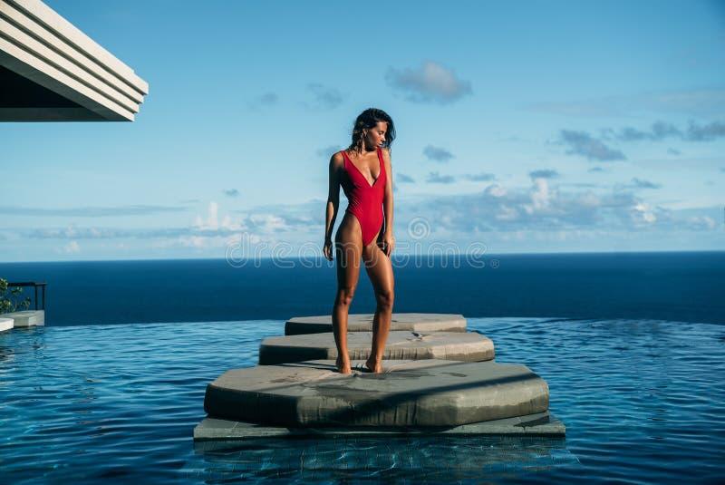 的性感的女孩放松在与海洋的游泳池的英俊的观点在背景 红色比基尼泳装摆在的逗人喜爱的少妇 图库摄影