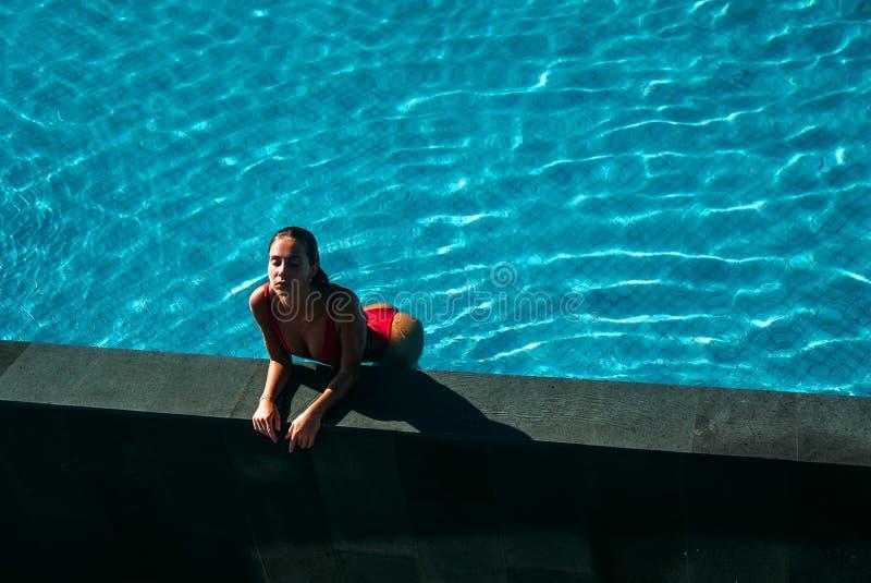 的性感的女孩放松在游泳池的惊人的观点 相当红色比基尼泳装摆在的少妇 泳装的概念 免版税库存照片