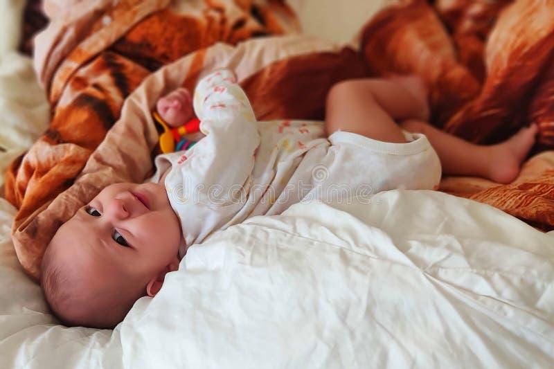 的愉快的婴儿婴孩在床上善意的谎言和获得乐趣 库存图片