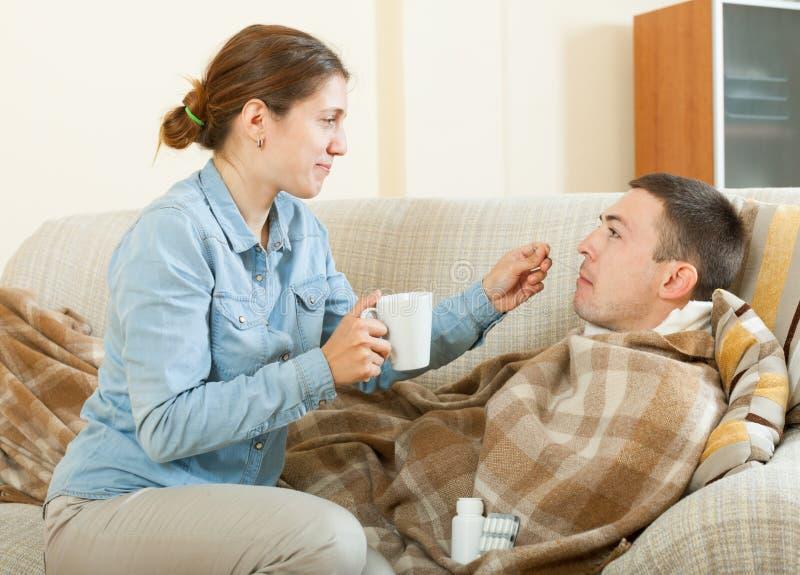 给给的成人女孩服麻醉剂给害病的人 免版税库存照片