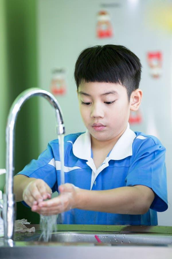 洗他的手的小亚裔男孩在厨房屋子 免版税库存图片