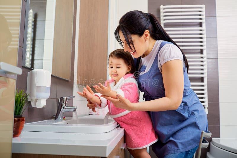 洗他们的手的母亲和女儿在卫生间里 关心  库存照片