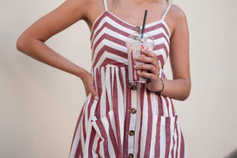 的时髦的年轻女人时兴的桃红色sundress在手中拿着可口草莓奶昔 时髦女孩喝一个冷饮 免版税库存照片