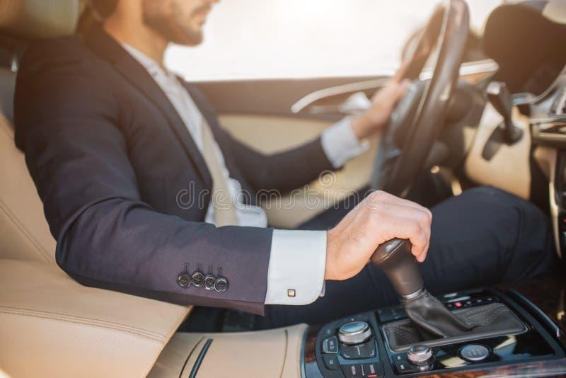 的有胡子的年轻人坐在汽车和驾驶的裁减观点 他握在方向盘和另一个的一只手  免版税库存照片