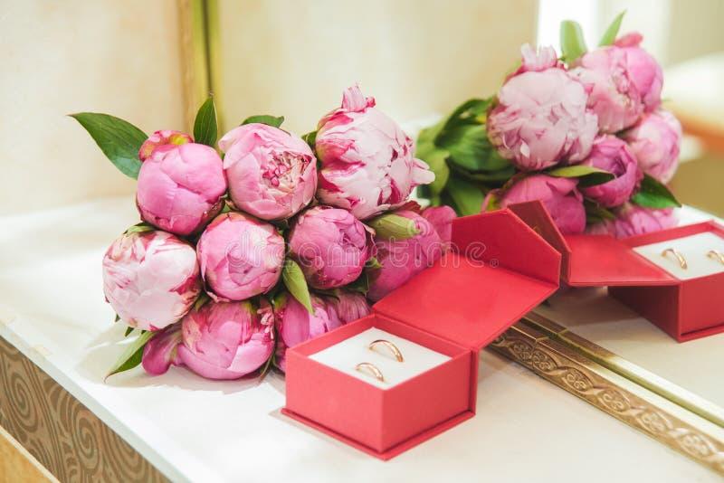 的桃红色牡丹和结婚戒指美丽的精美婚姻的在一个红色箱子的花束新娘和新郎 免版税库存照片