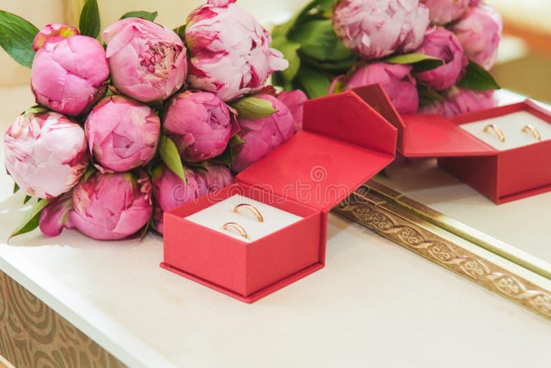 的桃红色牡丹和结婚戒指美丽的精美婚姻的在一个红色箱子的花束新娘和新郎 免版税图库摄影