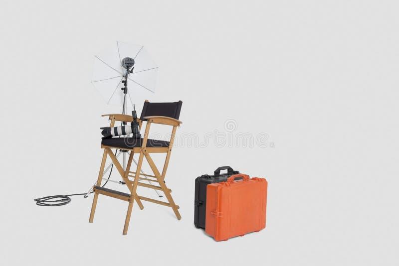 主任的椅子和反射器伞带着手提箱在演播室 免版税库存图片