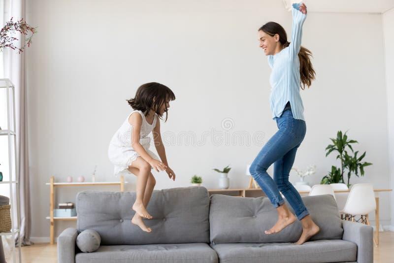 的母亲和获得一点的女儿跳跃在长沙发的乐趣 免版税图库摄影