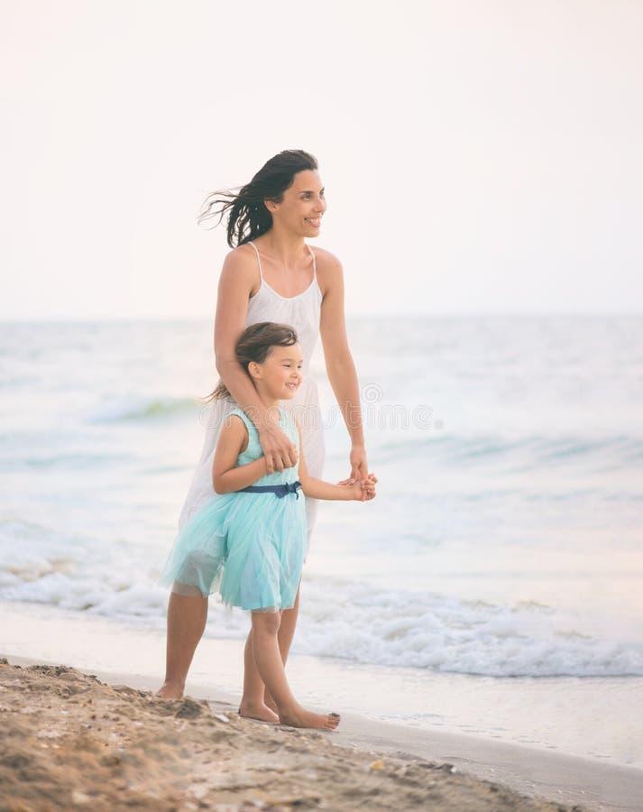 的母亲和获得她的女儿在海滩的乐趣 图库摄影