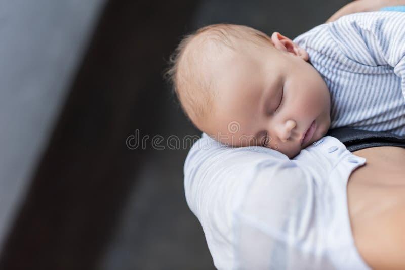 的母亲抱她睡觉的婴儿孩子的播种的观点 图库摄影