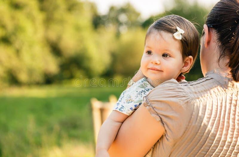 的母亲拿着她的胳膊的后面观点女婴 免版税库存照片