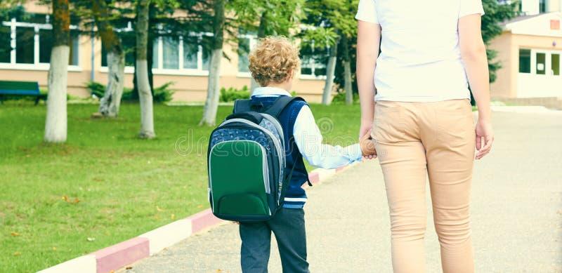 的母亲握小儿子的手的有背包的后面观点户外,回到学校 免版税图库摄影