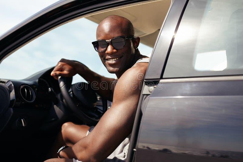 他的汽车的愉快的年轻人 图库摄影