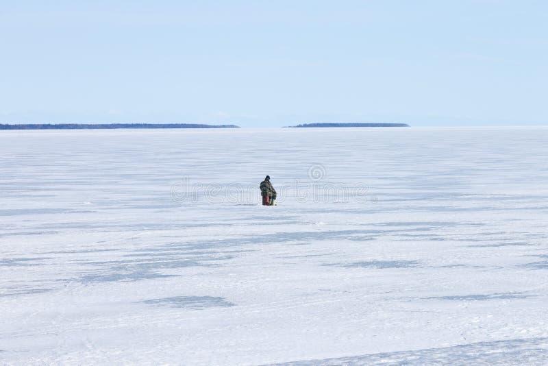 冻结的湖边钓鱼冰孔的孤独的渔夫 库存照片