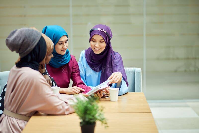 的照片愉快的回教不同种族的女学生的谈论书在图书馆 免版税库存照片