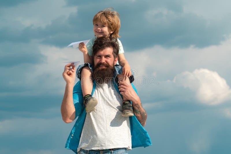 的父亲和使用他的儿子儿童的男孩户外 给在天空的愉快的父亲儿子乘驾在夏天 r ?? 库存照片