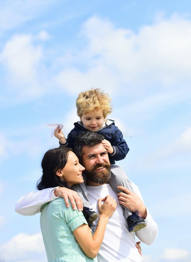 的父亲和使用他的儿子儿童的男孩户外 r 给在天空的愉快的父亲儿子乘驾在夏天 图库摄影