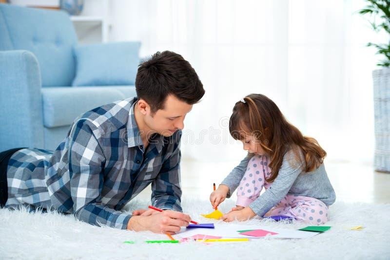 的父亲和有一点的女儿质量家庭时间一起在家 有说谎在与五颜六色的温暖的地板图画的女孩的爸爸 库存照片