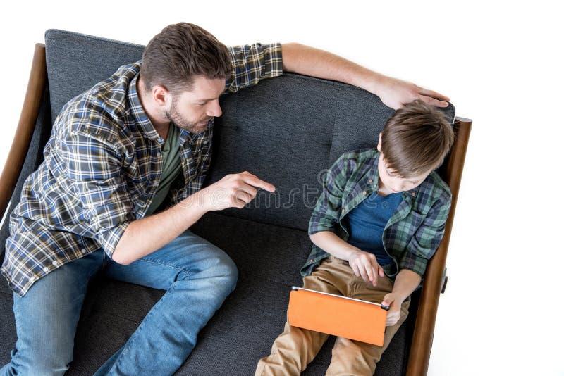 的父亲坐沙发和指向与手指的大角度观点使用数字式片剂的儿子 库存图片