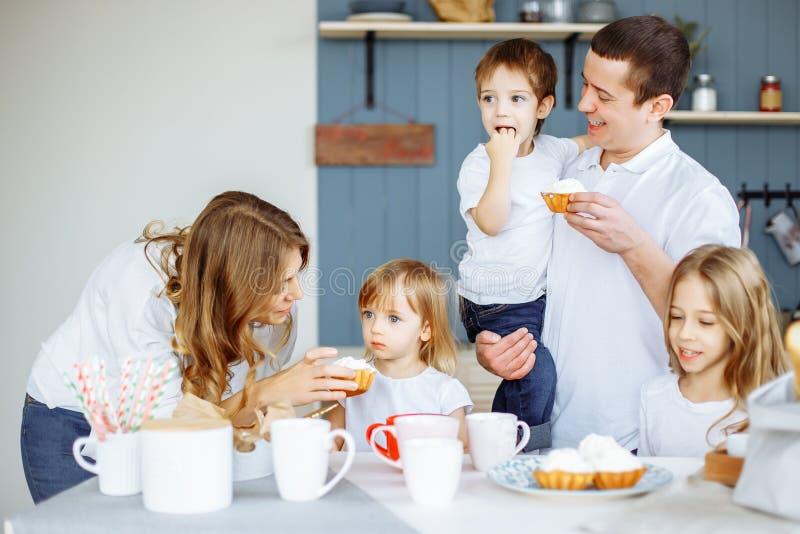 的父母和一起享用他们的三个的孩子吃在厨房里和 免版税库存图片