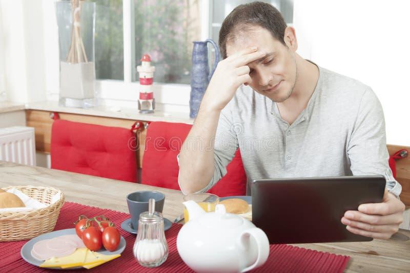 读他的片剂的可爱的人在桌上 免版税图库摄影