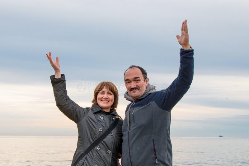 的男人和附近站立的妇女举了他们的在问候的手 海和天空在背景中 库存照片