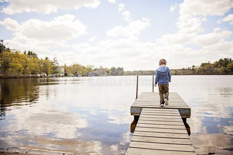 的男孩走在船坞的后面观点在湖 图库摄影
