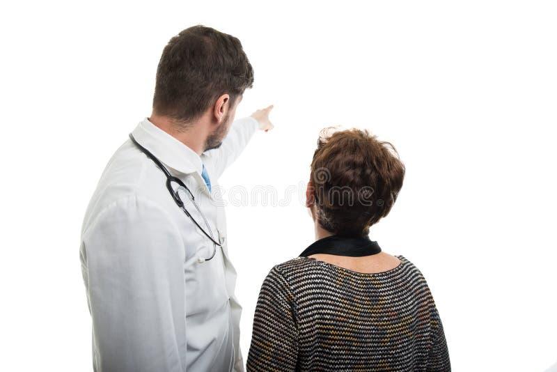 的男性医生指向女性资深患者的后面观点 免版税图库摄影
