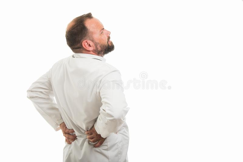 的男性医生显示背部疼痛姿态的后面观点 库存照片