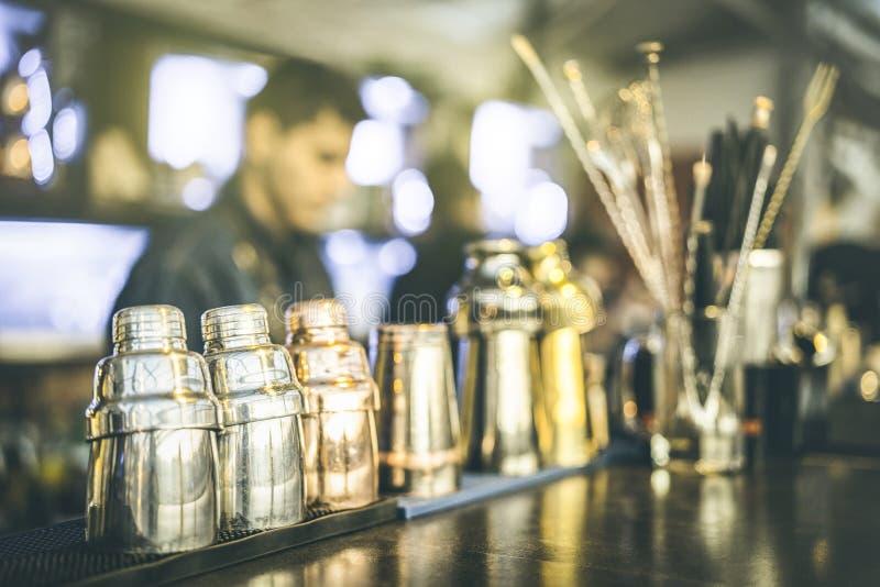 的男服务员准备饮料的被弄脏的defocused观点在酒店鸡尾酒吧在快乐时光-与模糊的侍酒者的混合酒调制术概念 免版税库存图片