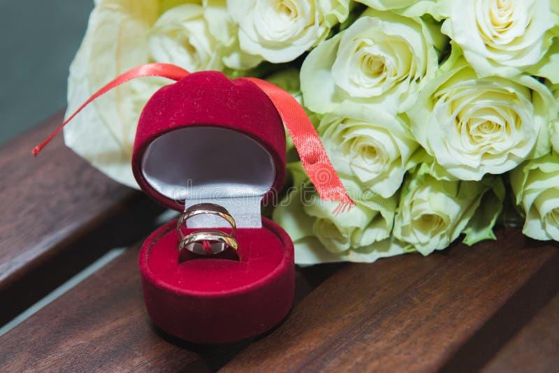 的白玫瑰和结婚戒指美丽的精美婚姻的在一个红色箱子的花束新娘和新郎 免版税库存图片