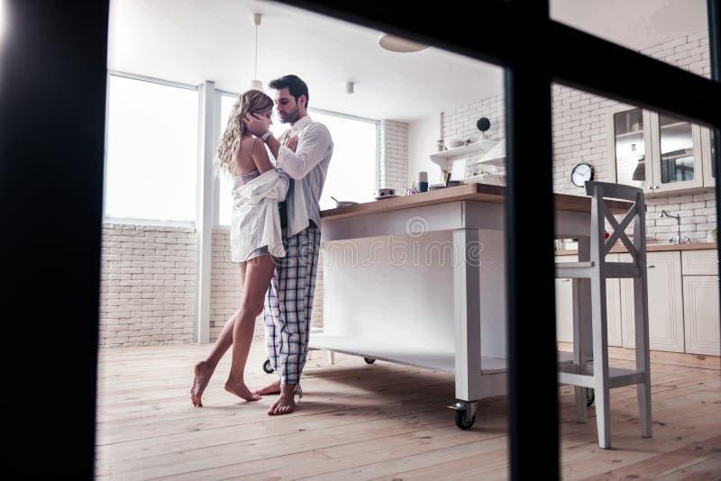 的白色衬衫和看起来他美丽的妻子的深色头发的有胡子的人周道 免版税库存照片