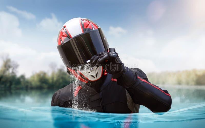的盔甲和充满充分的齿轮的摩托车骑士 人是一半水中 库存图片