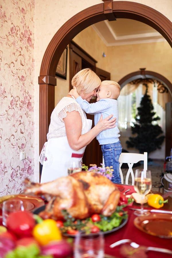 的祖母和获得的小男孩在感恩的乐趣在被弄脏的背景 家庭假日概念 库存照片