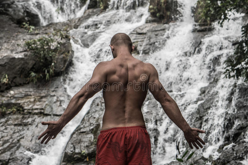 的肌肉人站立与被举的胳膊的后面观点临近瀑布 库存照片