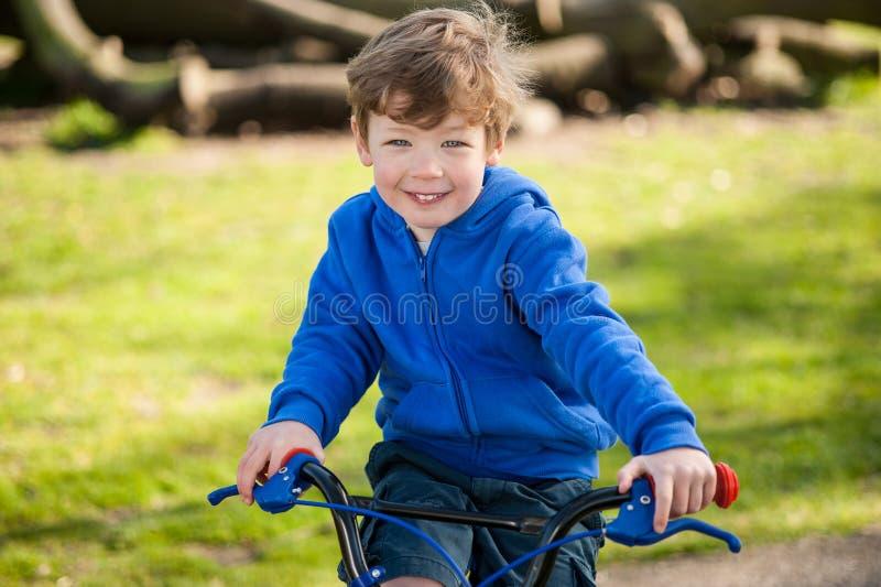 他的自行车的愉快的男孩在公园 库存图片