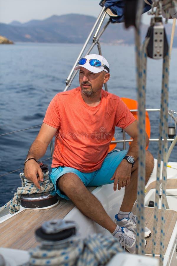 他的航行游艇小船的人 体育运动 免版税库存照片