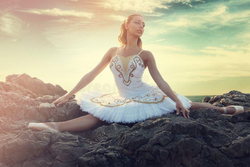 年轻的芭蕾舞女演员做分裂在岩石 免版税库存图片