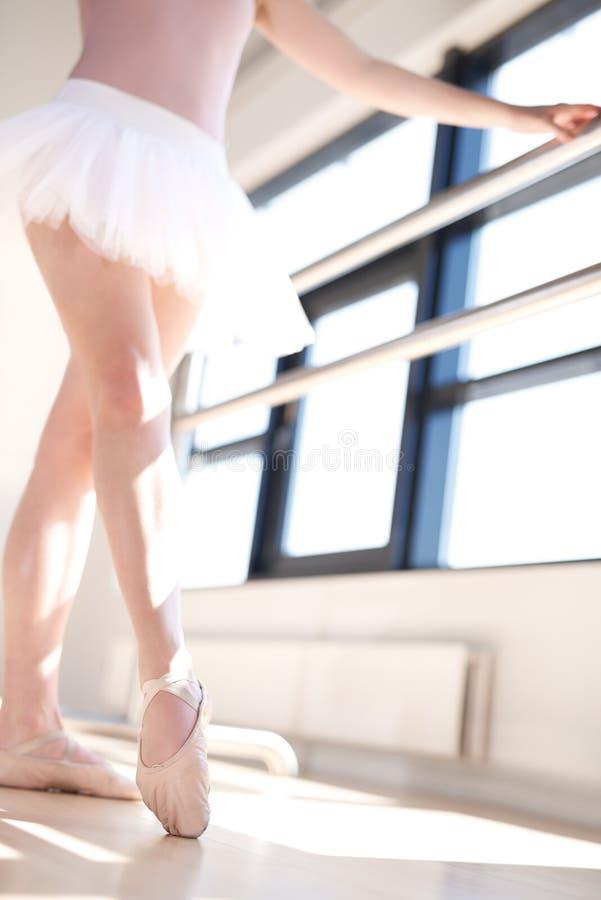 的芭蕾舞女演员做纬向条花锻炼的低角度观点 库存照片