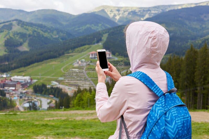 的苗条妇女在两只手中的后面观点拿着她的智能手机,旅行博克的照相,在网上寻找新的路线, 免版税库存照片