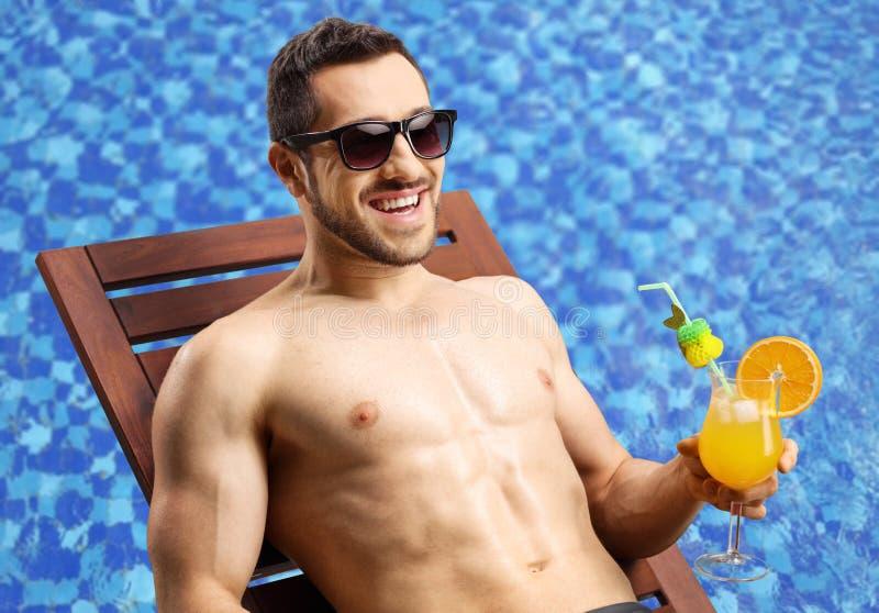 的英俊的年轻人sunbed与鸡尾酒 库存照片