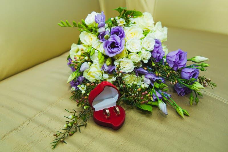 的蓝色玫瑰和结婚戒指美丽的婚姻的在一个红色箱子的花束新娘和新郎以心脏的形式 免版税图库摄影