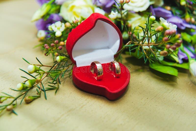的蓝色玫瑰和结婚戒指美丽的婚姻的在一个红色箱子的花束新娘和新郎以心脏的形式 免版税库存照片