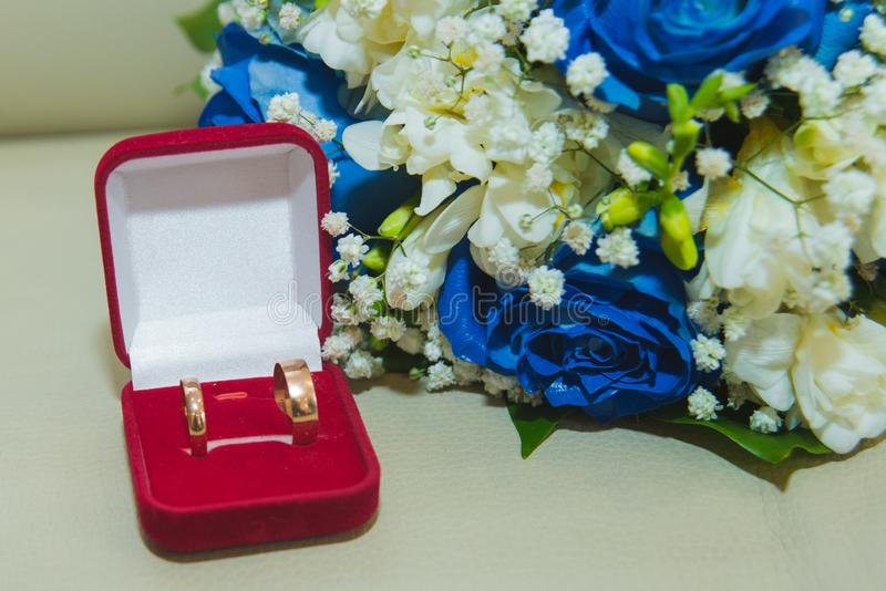 的蓝色玫瑰和结婚戒指美丽的精美婚姻的在一个红色箱子的花束新娘和新郎 免版税图库摄影