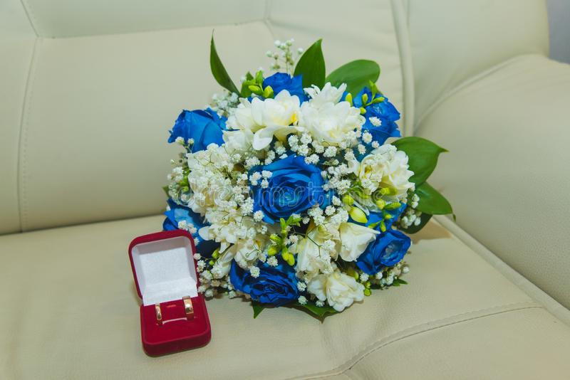 的蓝色玫瑰和结婚戒指美丽的精美婚姻的在一个红色箱子的花束新娘和新郎 免版税库存图片
