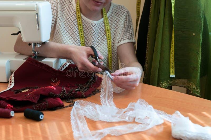 的裁缝坐在与缝纫机的桌上和切开鞋带的播种的观点 免版税库存图片