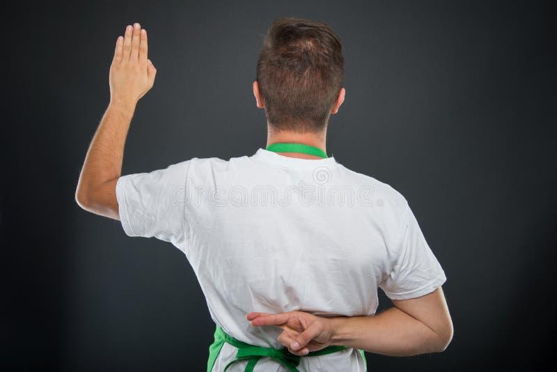 的超级市场雇主做假誓言姿态的后面观点 库存照片
