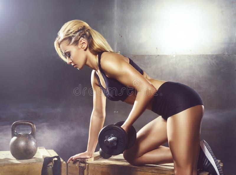 的适合和有运动的女孩训练 地下健身房 健康,体育,健身概念 库存图片