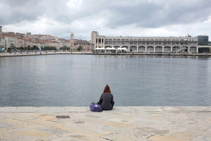 的里雅斯特, 2017年9月5日,意大利:女孩单独坐一个石码头 免版税库存照片