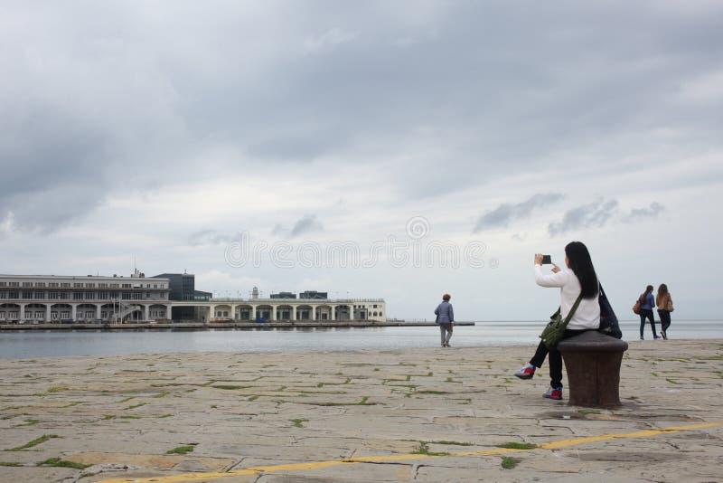 的里雅斯特, 2017年9月5日,意大利:女孩坐拍与她巧妙的电话的一个石码头照片 免版税图库摄影